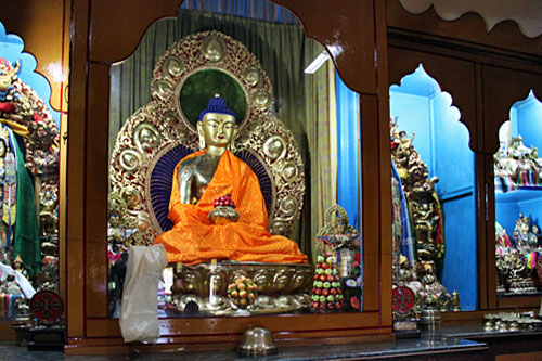 Buddha sits behind glass on altar at Shree Gaden Dhargay Ling Monastery