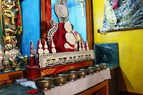 Yak butter carving and seven bowls of water sit in front of Buddha on the altar
