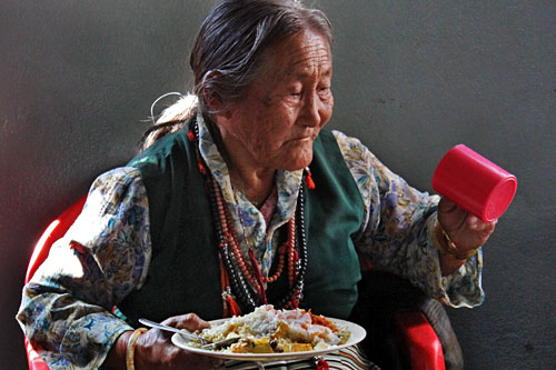 Tibetan woman enjoys meal at International Human Rights Day Celebration at Tashiling Tibetan refugee settlement in Pokhara, Nepal