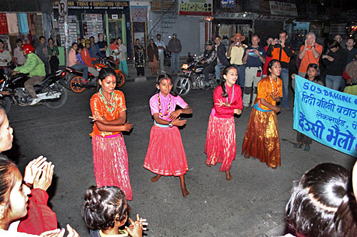Dancers perform in the streets of Pokhara for donations on the third evening of the Tihar Festival